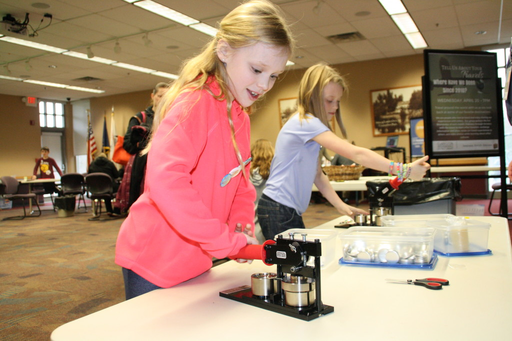 From left, sisters Anna and Aubrey Reineck use presses to make buttons at the Clarkston Independence District Library's Maker Magic event during spring break. Photo by Trevor Keiser
