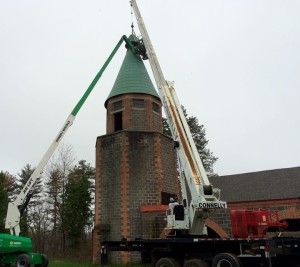 Construction crews hang the bell in the Brady Lodge tower.