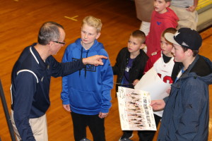 Dan Fife gives tips to youngsters as he signs their posters after the game, March 3. Photo by Wendi Reardon Price
