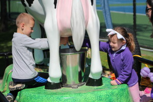 Joey and Lizzie Rickard try out milking a cow at the Oakland County Fair booth. The fair is at Springfield Oaks County Park, July 7-16.  Photo by Wendi Reardon Price