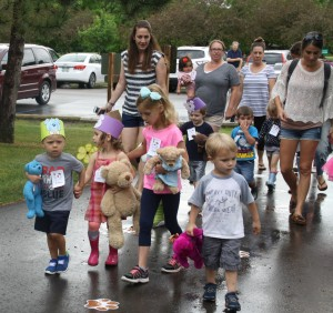 Kids walk with their stuffed animal friends in the parade.