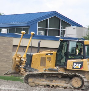 A construction worker drives a bulldozer in front of Bailey Lake Elementary. Photo by Jessica Steeley