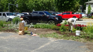 Volunteers weed and plant flowers in the garden next to the Clarkston News building. Photo provided