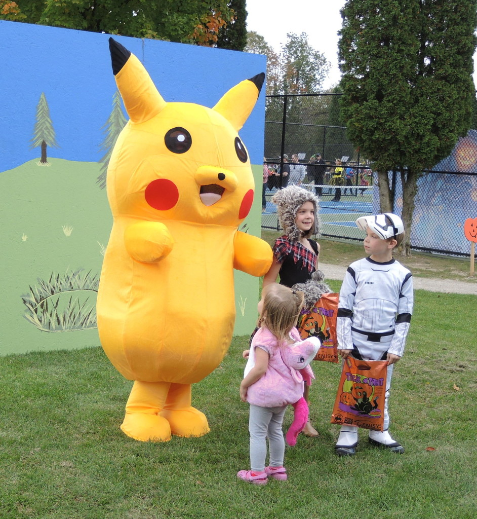 Lilly, Gage, and Lucy Pittman visit with Pikachu, played by volunteer Sara Harker, at Friendly Forest,