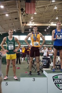 Scott Cousino stands on the podium and proudly displays his medal for finishing in third place in the 800-meter run during the MAC Indoor Track & Field Championships. Photo submitted