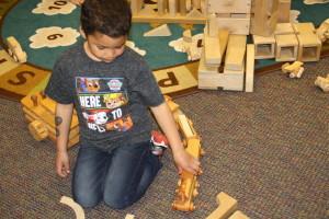 Preschooler Braydan Odneal playing with a wooden train made by Robert Jones