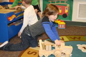 Preschooler Laine York playing with a wooden tractor made by Robert Jones 4