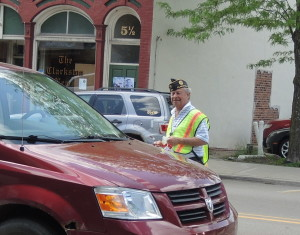 Tom Phipps of American Legion Post 63 collects donations for veterans during the post's poppy drive on Main Street, May 19.