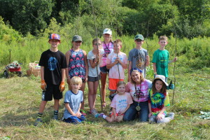Kids in Camp Wild take a moment for a group picture while looking for branches for their wigwam. Photo by Wendi Reardon Price